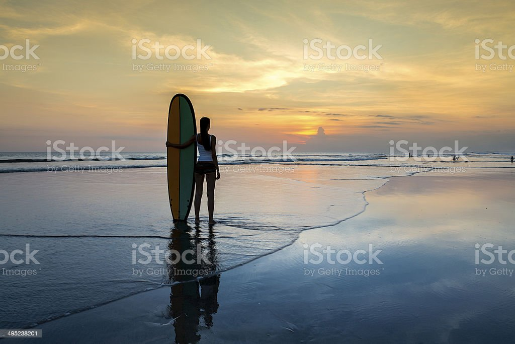 Woman with surf board on the beach at sunset stock photo