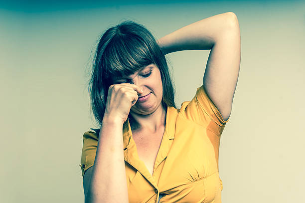 Woman with sweating under armpit in yellow dress Young woman with sweating under armpit in yellow dress isolated on gray - retro style wet clothing women t shirt stock pictures, royalty-free photos & images
