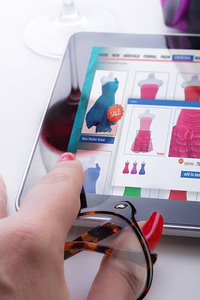 frau mit tablet und glas wein kauft online-kleid - dresses online shop stock-fotos und bilder