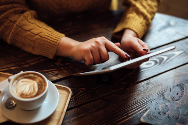 Woman with tablet behind table in cafe stock photo