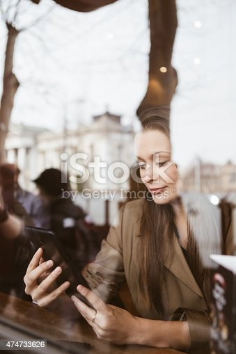 Beautiful young woman using tablet at caffe shop, seen through window.