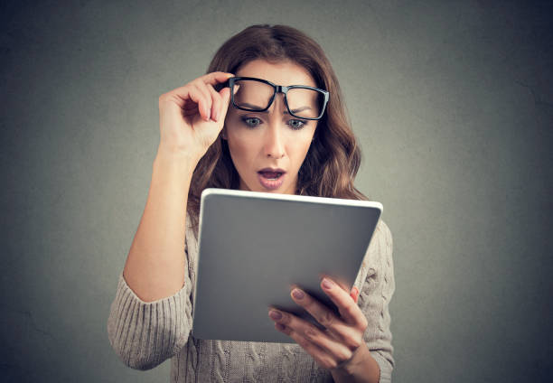 Woman with tablet looking shocked stock photo