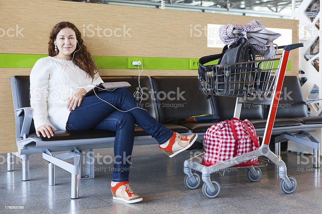 Woman with tablet pc charging devices in airport royalty-free stock photo
