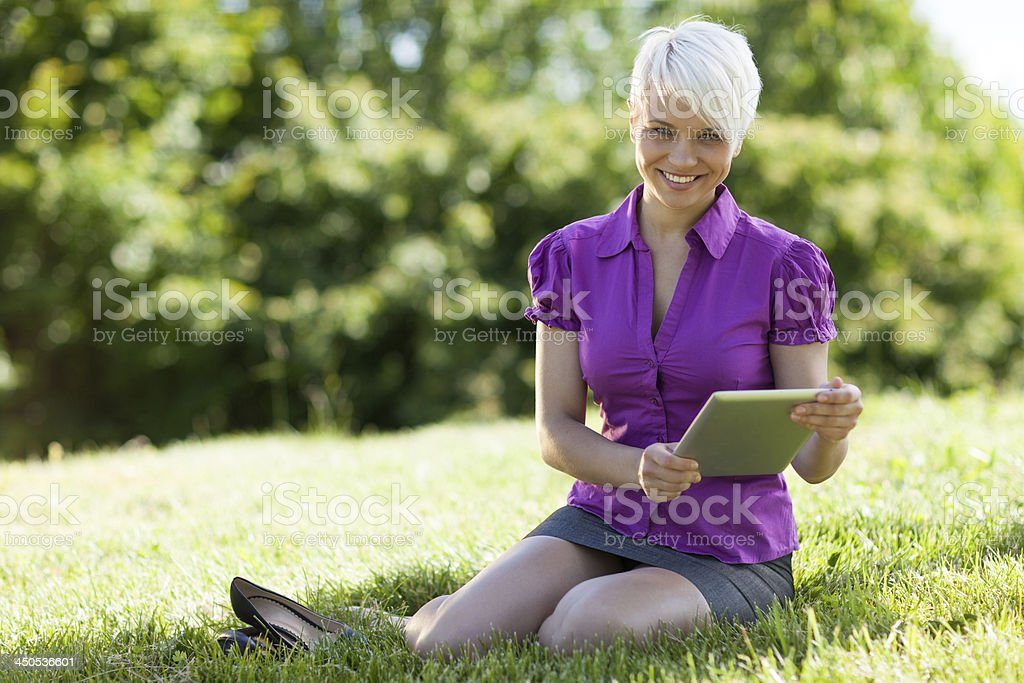 Woman with tablet pc is sitting on the grass stock photo