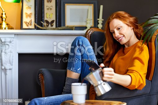 Smiling young woman holding digital tablet while pouring coffee into cup. Beautiful female is with wireless technology and refreshment at home. She is wearing casuals.