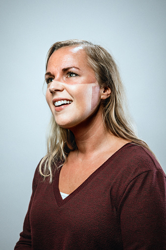 A humorous portrait of a smiling woman who after getting a slight sunburn while wearing her PPE now has a face mask tan-line.  Finding humor during a the global pandemic of Covid-19 / Coronavirus.