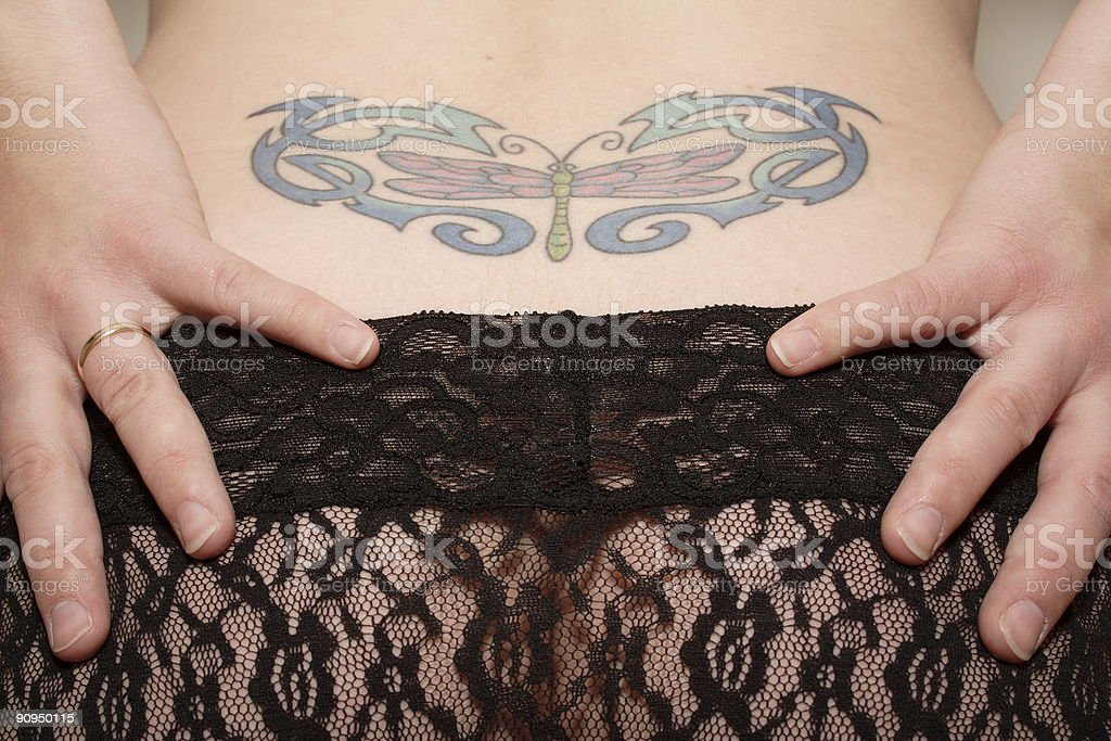 Woman with tattoo and hands on panties royalty-free stock photo