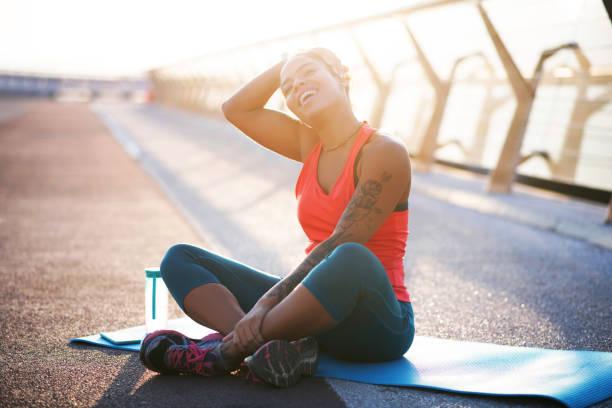frau mit tattoo auf arm lieben sport üben yoga draußen - damen leggings übergrößen stock-fotos und bilder