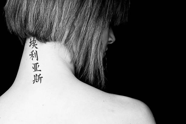 frau mit tattoo - chinesische zeichen tattoos stock-fotos und bilder