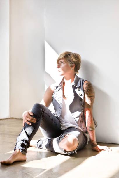 Frau mit Tattoo sitzt auf dem Boden und schaut weg – Foto
