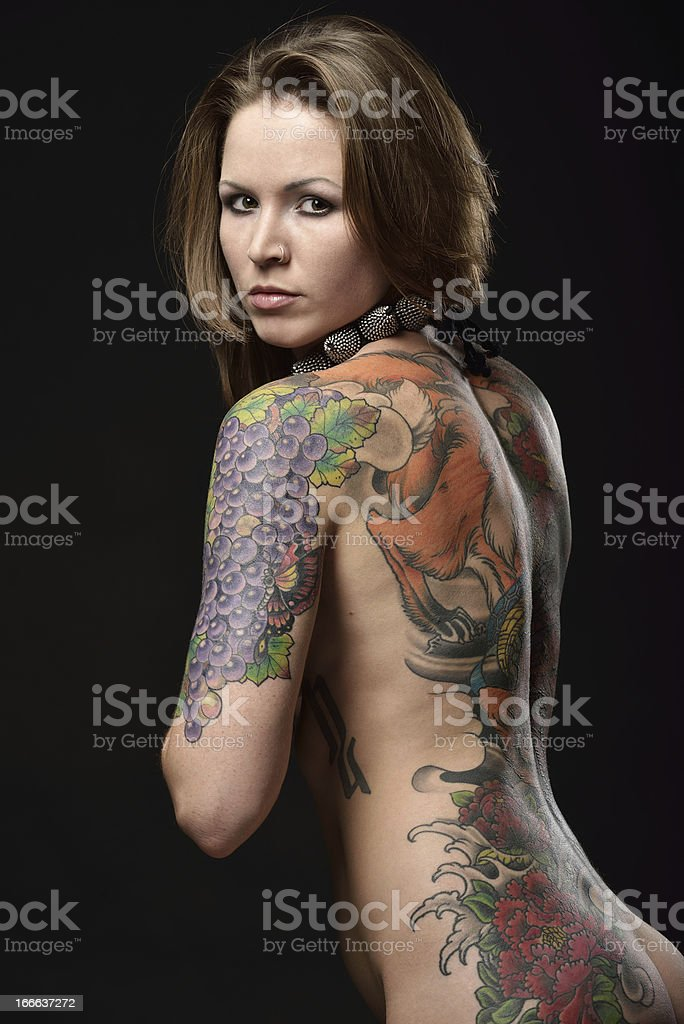 Woman with tattooed back posing against black background royalty-free stock photo
