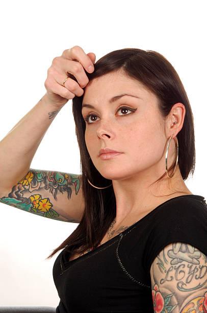 frau mit tattoos und piercings und ohrringe - molekül tattoo stock-fotos und bilder