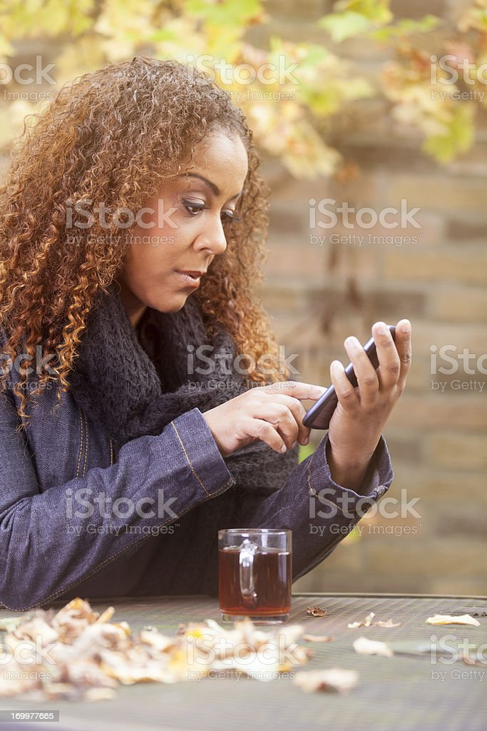Woman with tea and smartphone stock photo