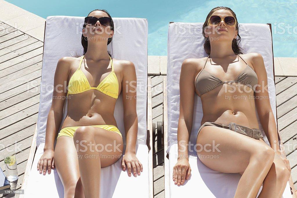 Femme avec des jeunes amis allongé sur une chaise longue près de la piscine - Photo
