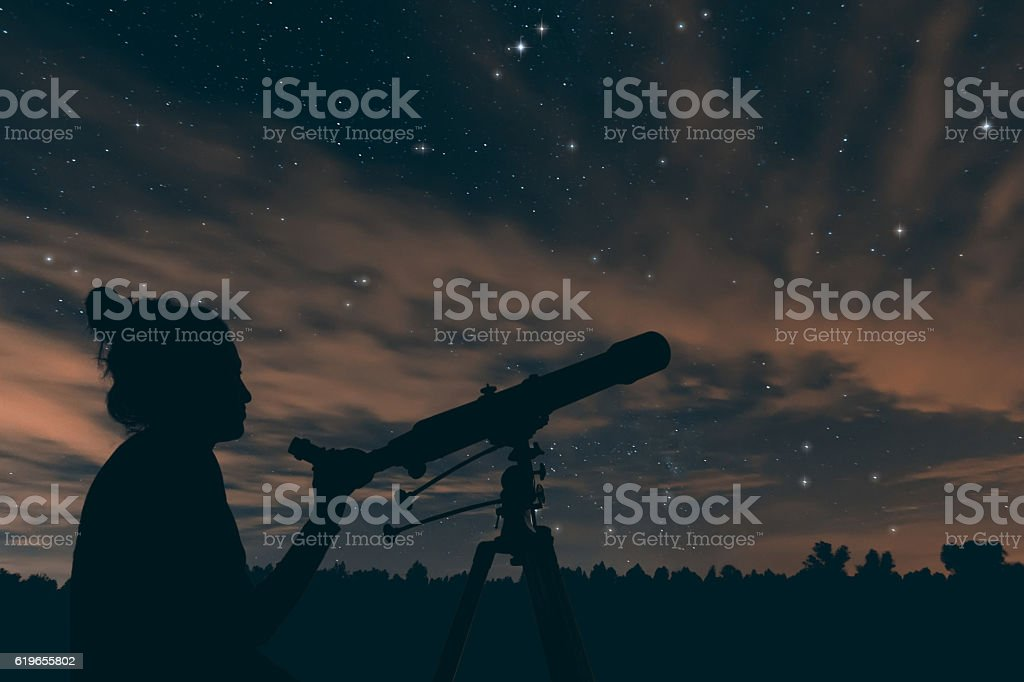 Woman with telescope. Night sky, with clouds and constellations, stock photo