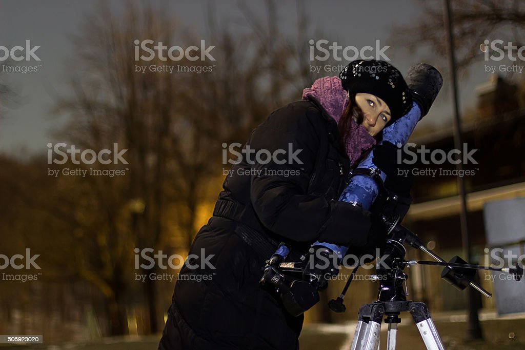 Woman with telescope under winter night sky stock photo