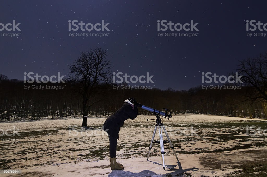 Woman with telescope under winter starry night sky stock photo