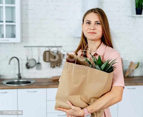 istock woman with the grocery store packet in the hands. 1219232786