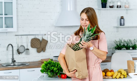 istock woman with the grocery store packet in the hands. 1219232788