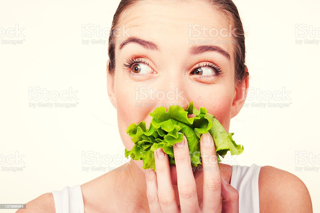 Woman with the lettuce in her mouth. stock photo