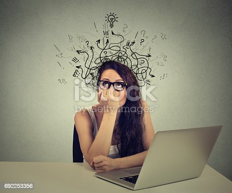 istock woman with thoughtful expression sitting at a desk with laptop with lines arrows and symbols coming out of her head 692253356