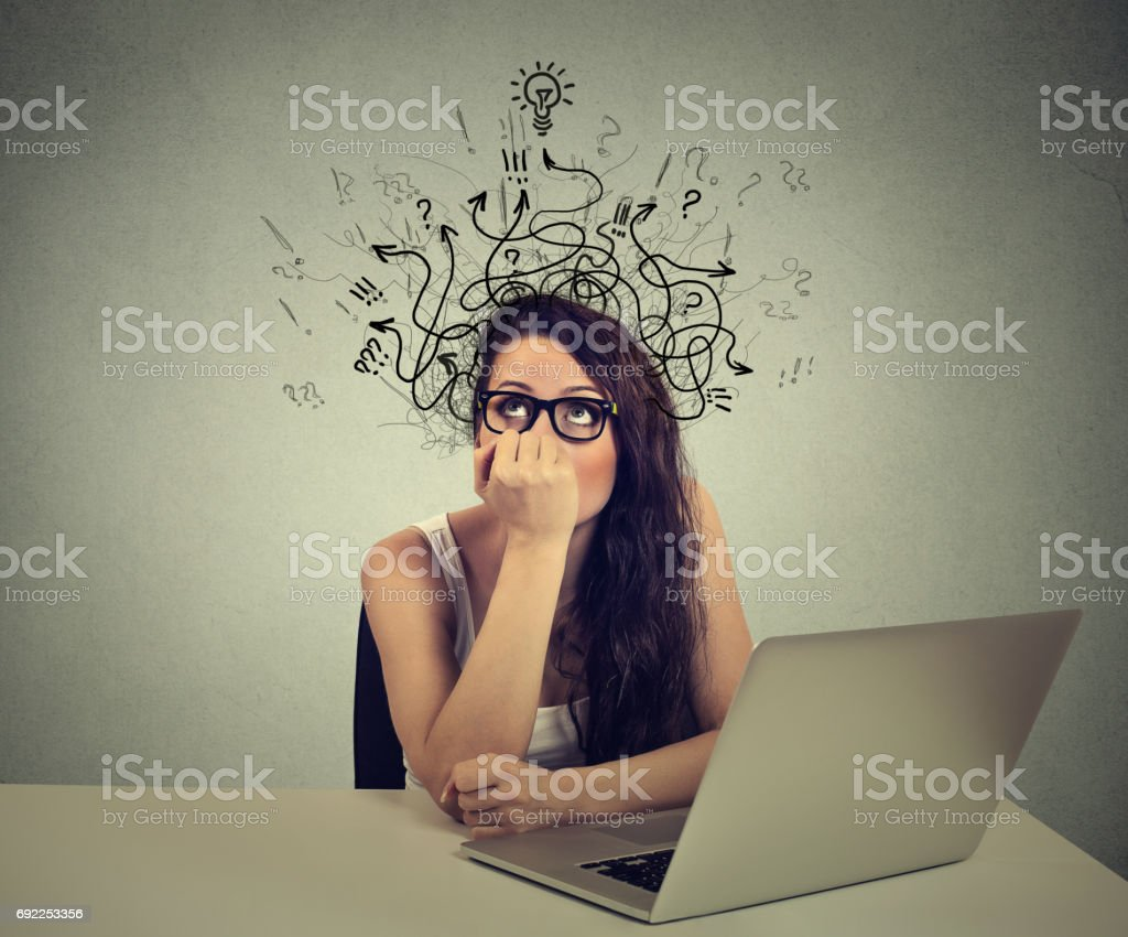 woman with thoughtful expression sitting at a desk with laptop with lines arrows and symbols coming out of her head – zdjęcie