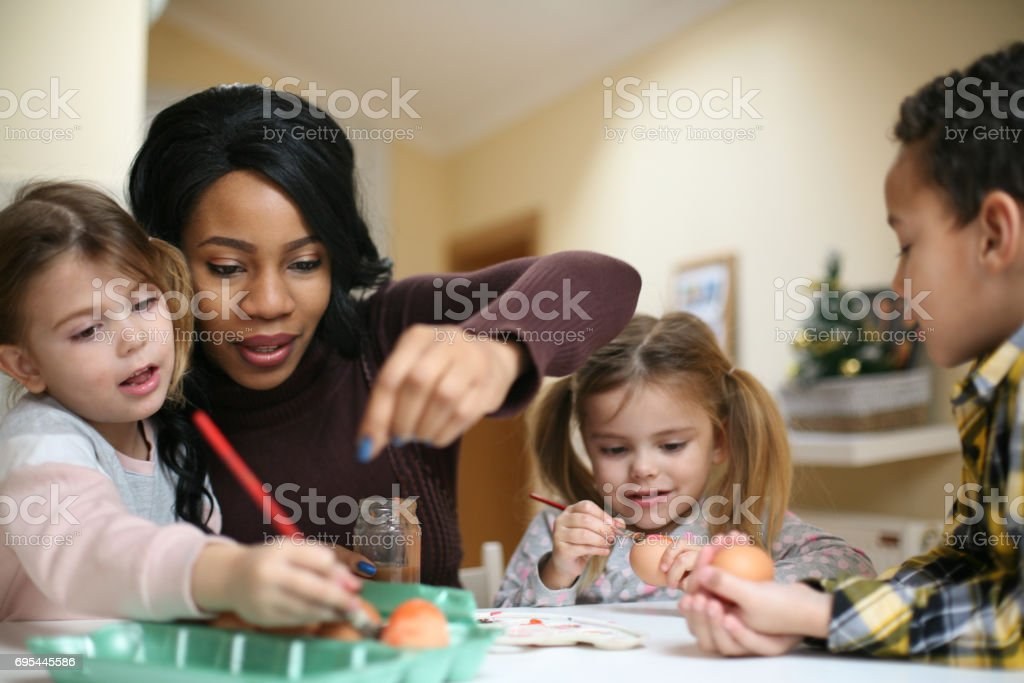 Woman with three child. African American woman with three child prepare for Easter. stock photo