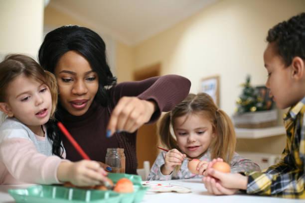 Mujer con tres hijos. Mujer afroamericana con tres niños se preparan para Semana Santa. - foto de stock