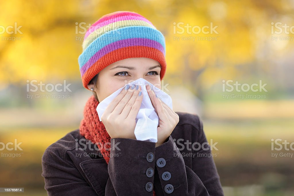Young woman with tissue having flu or allergy