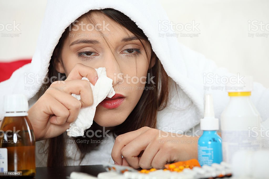 Woman with tissue leaning on table surrounded by medicine royalty-free stock photo