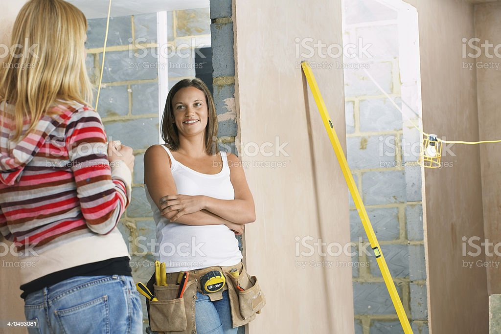 Woman With Toolbelt Talking To Friend royalty-free stock photo