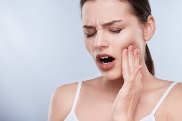 Woman with toothache Toothache, white teeth. Head and shoulders of young woman suffering from toothache, teethcare. Painful expression on face of woman, hands near face, closed eyes toothache stock pictures, royalty-free photos & images