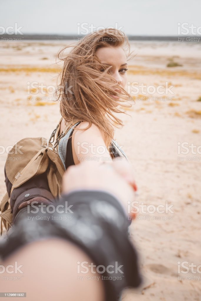 Woman with tousled hair holding friend's hand Portrait of beautiful woman with tousled hair holding friend's hand. Females are enjoying in desert. They are spending summer vacation. 20-24 Years Stock Photo