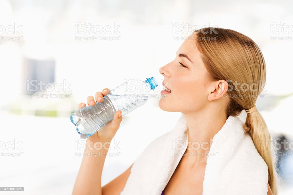 Woman With Towel Around Neck Drinking Water At Gym royalty-free stock photo