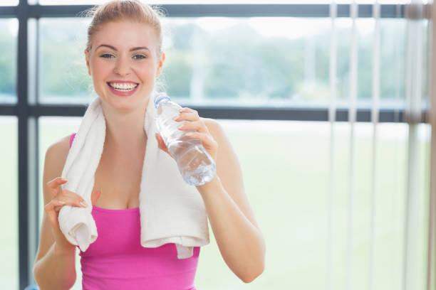 frau mit handtuch um den hals halten wasser flasche - rosa training stock-fotos und bilder