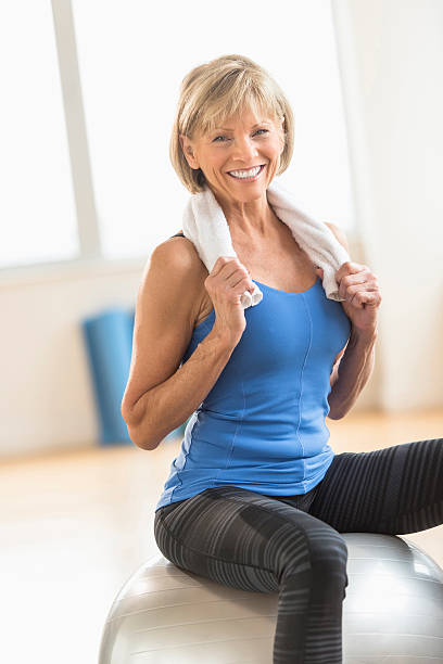 Woman With Towel Around Neck Sitting On Fitness Ball stock photo