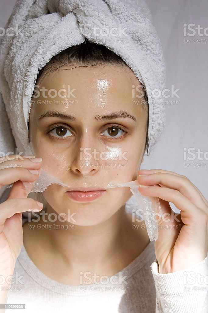 Woman with towel on head peeling off a collagen mask royalty-free stock photo