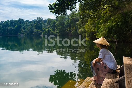 Woman with traditional hat relaxing on water's edge of volcanic lake surrounded by forest in Banlung, Cambodia, travel destination in Asia