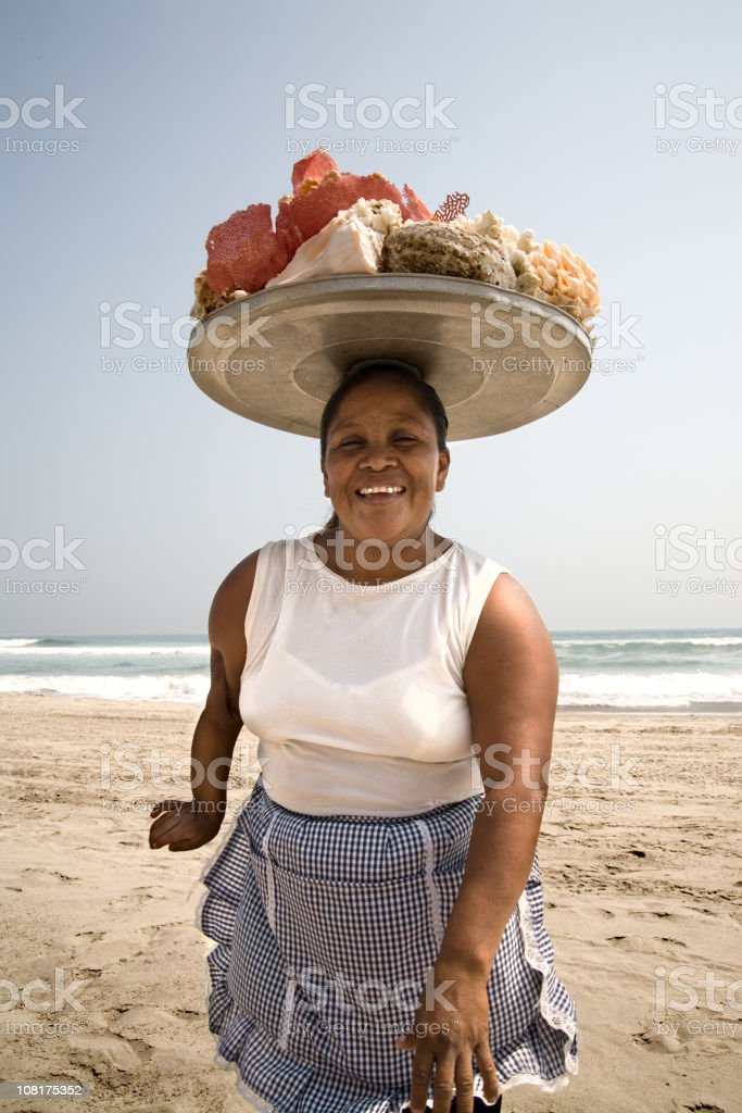 Woman with Tray of Shells on Head at Beach royalty-free stock photo