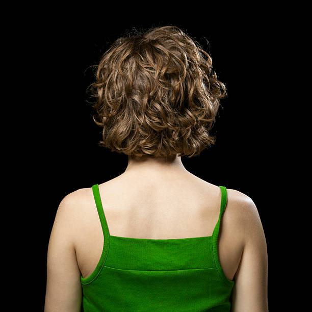 Woman with Twisted Strap Rear view of young woman in top with one strap twisted against black background. spaghetti straps stock pictures, royalty-free photos & images