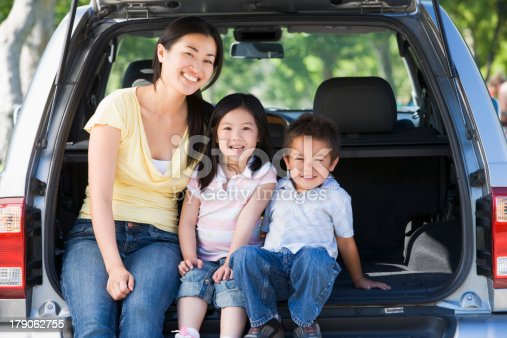 istock Woman with two children sitting in back of van smiling 179062755