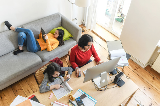 woman with two daughters working at home office in living room