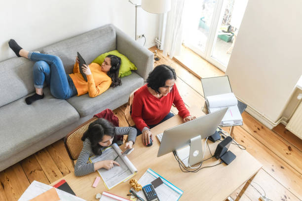 woman with two daughters working at home office in living room woman working at home in living room, daughters doing home work and hanging around quarantine stock pictures, royalty-free photos & images