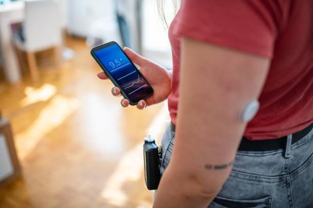 женщина с диабетом типа 1 проверка данных крови на телефоне app - medical technology стоковые фото и изображения