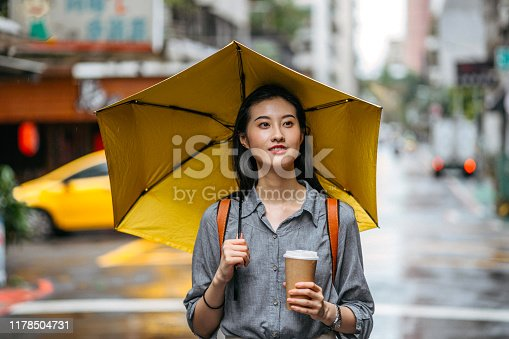 Taiwanese woman walking down the city street with umbrella and coffee on a rainy day