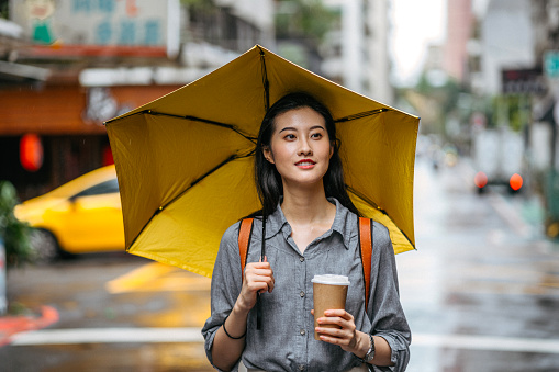 Woman with umbrella and coffee on rainy day
