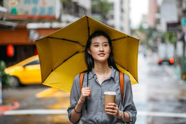 frau mit regenschirm und kaffee am regnertag - regenzeit stock-fotos und bilder