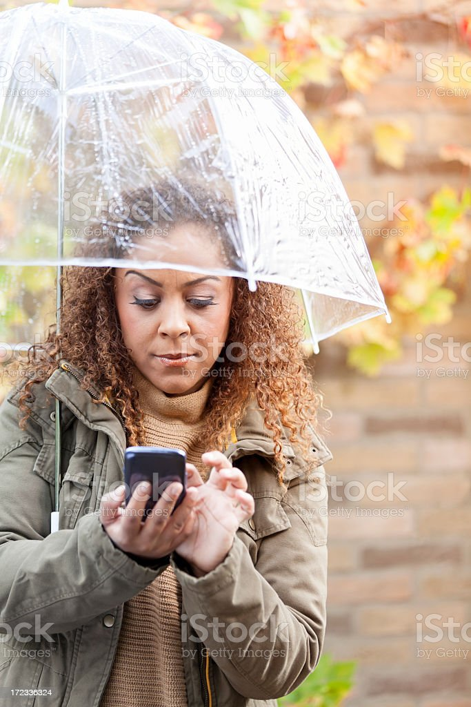 Woman with umbrella and smartphone royalty-free stock photo