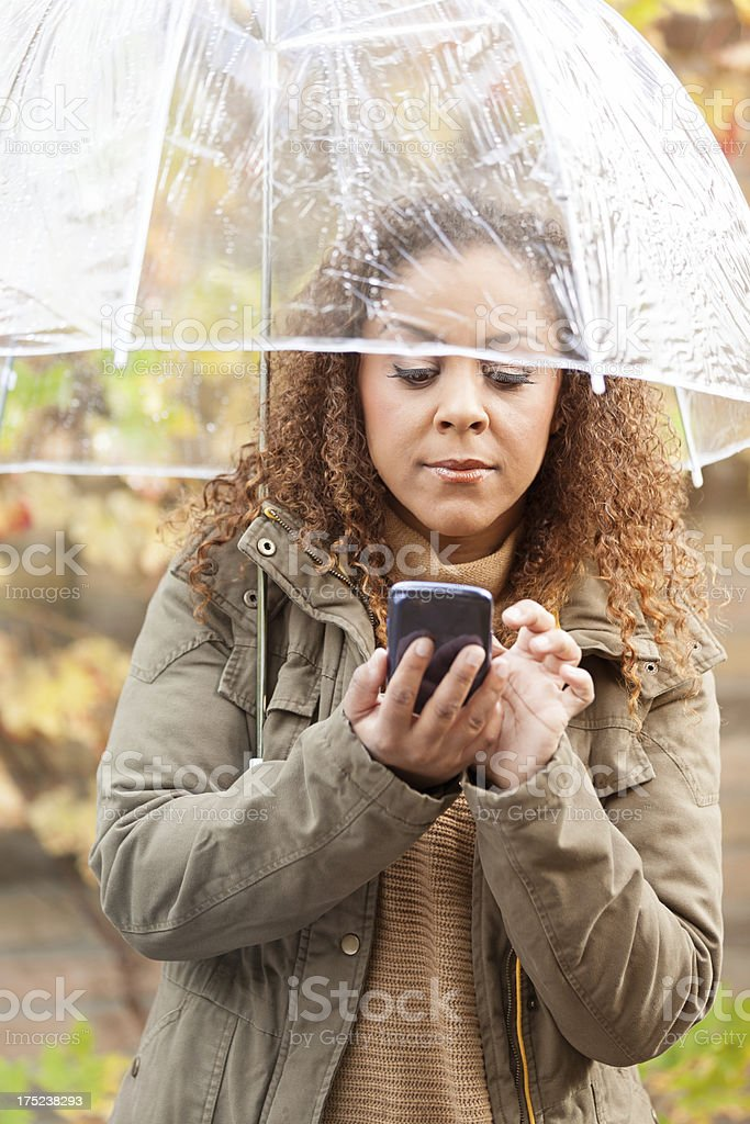 Woman with umbrella and smartphone stock photo