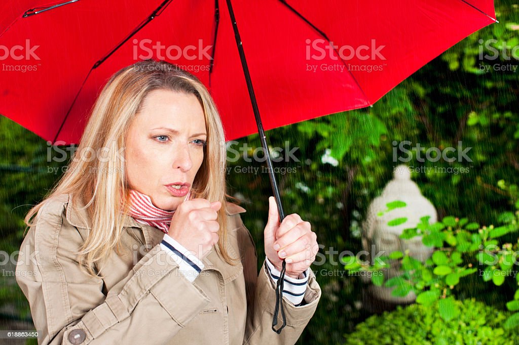 Woman with umbrella coughing stock photo
